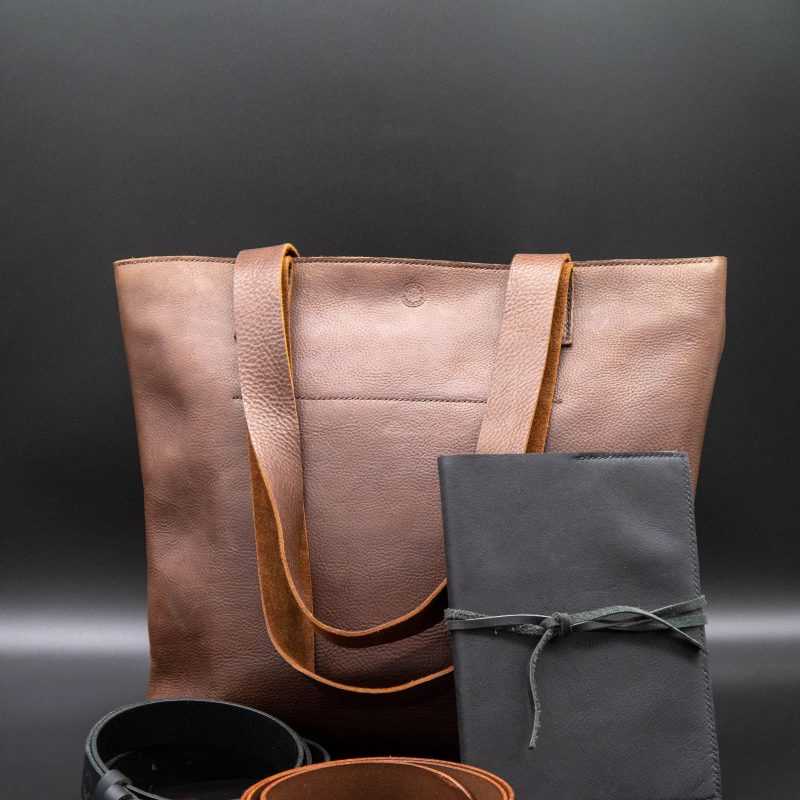 A selection of beautiful hand made leather goods including a brown tote bag, black journal and leather belts.