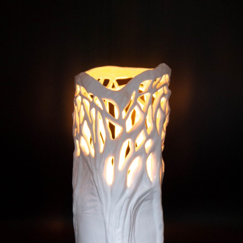 An elegant white sculpture in an abstract tree design.  The piece is hollow to allow a candle or fairy lights to be placed inside.