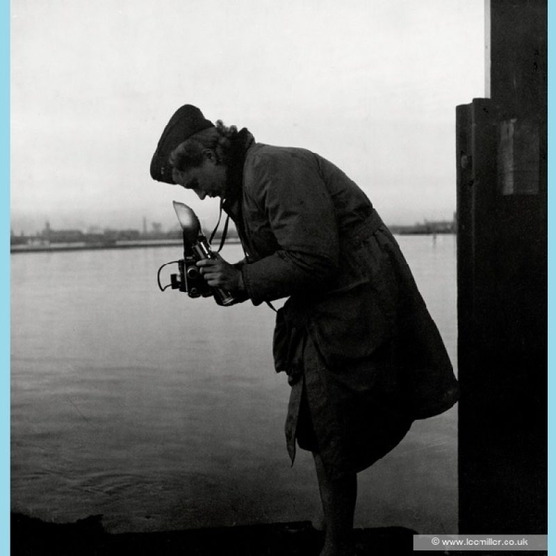 Full length profile of Lee Miller in uniform bending over camera, holding a flash gun at Portsmouth Harbour, water in background.