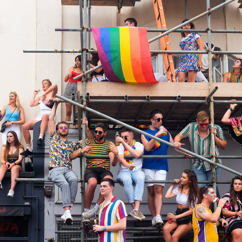 A colour photograph of some Pride revellers partying on some scaffolding. Taken at Brighton Pride 2019