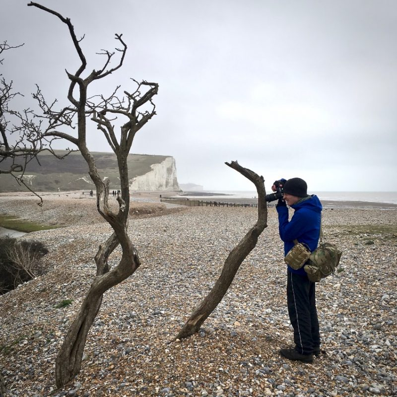 A man, right of centre, taking a photograph. He is wearing a blue coat and dark trousers. The white cliffs are in the background.