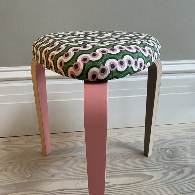 A cute 3 legged stool with two pink legs and one grey covered in Ola pink and green fabric.