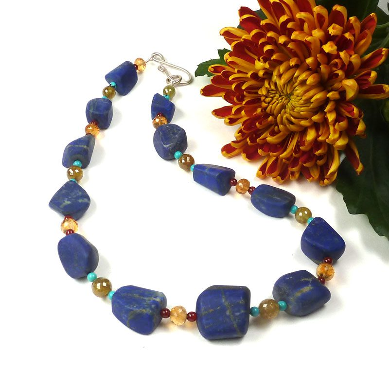 A statement necklace in which large pebbles of lapis lazuli are interspersed with citrine, green garnet, carnelian and turquoise.