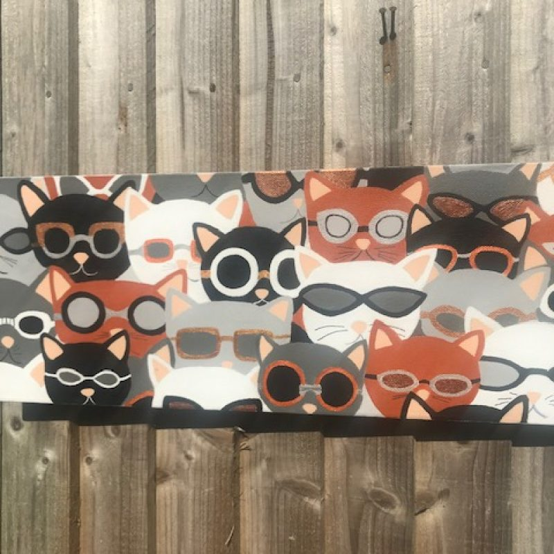A painting of several cats heads wearing sunglasses.