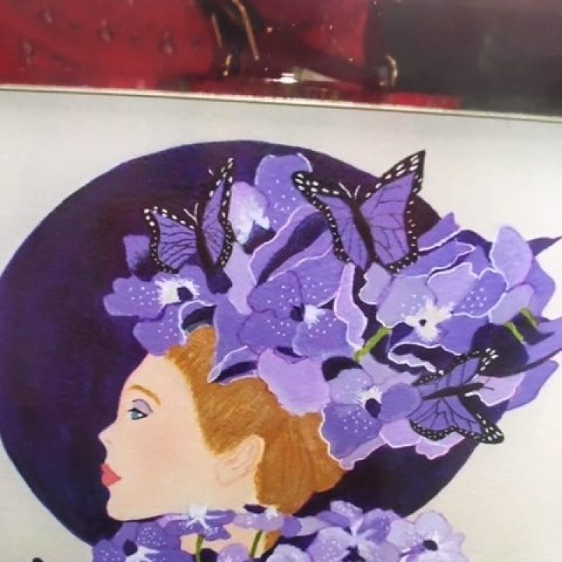 The head of a woman in a large purple hat decorated with orchids in shades of violet/lavender.