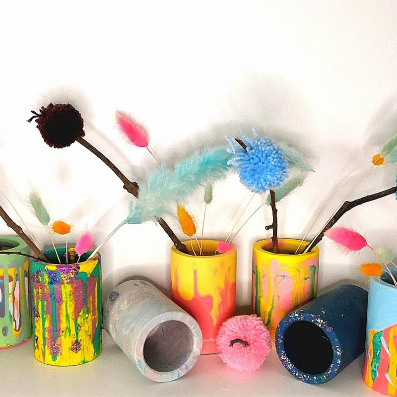 Image shows a range of colourful jesmonite vases with pom pom sticks and coloured bunny tails.
