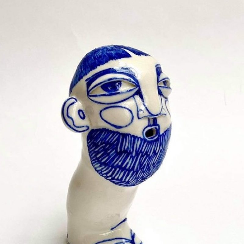 Porcelain figure of a head on one leg painted with cobalt blue decoration