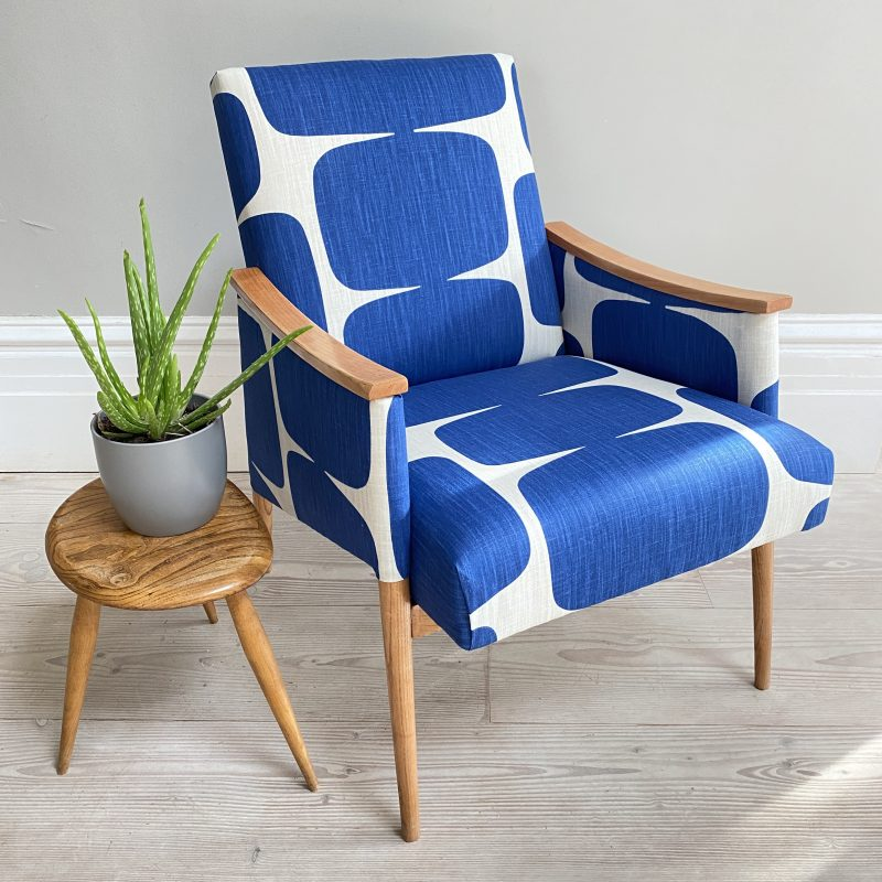 Small Armchair with tapered wooden legs and wooden armrests upholstered in bright blue geometric print.