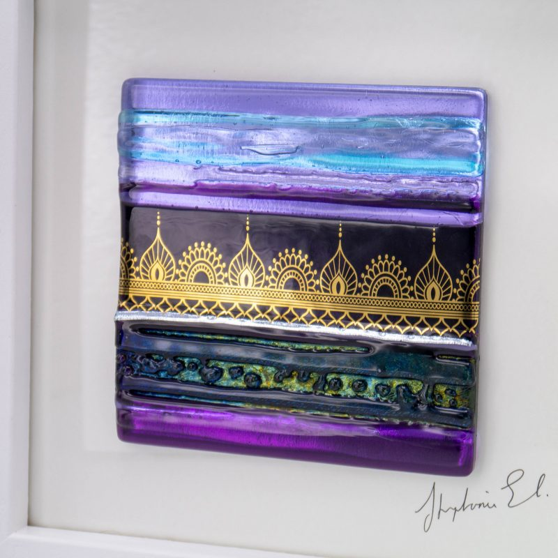 A violet and purple kiln-formed glass tile with a gold Indian inspired motif set in a chunky white wooden frame,