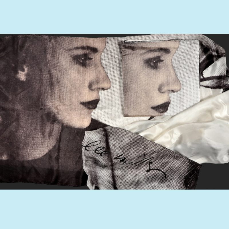 Silk scarf printed with images of Lee Miller's self portrait in profile and her image 'Portrait of Space', the desert in Egypt seen through a a torn screen. Subtle shades of grey and pink.
