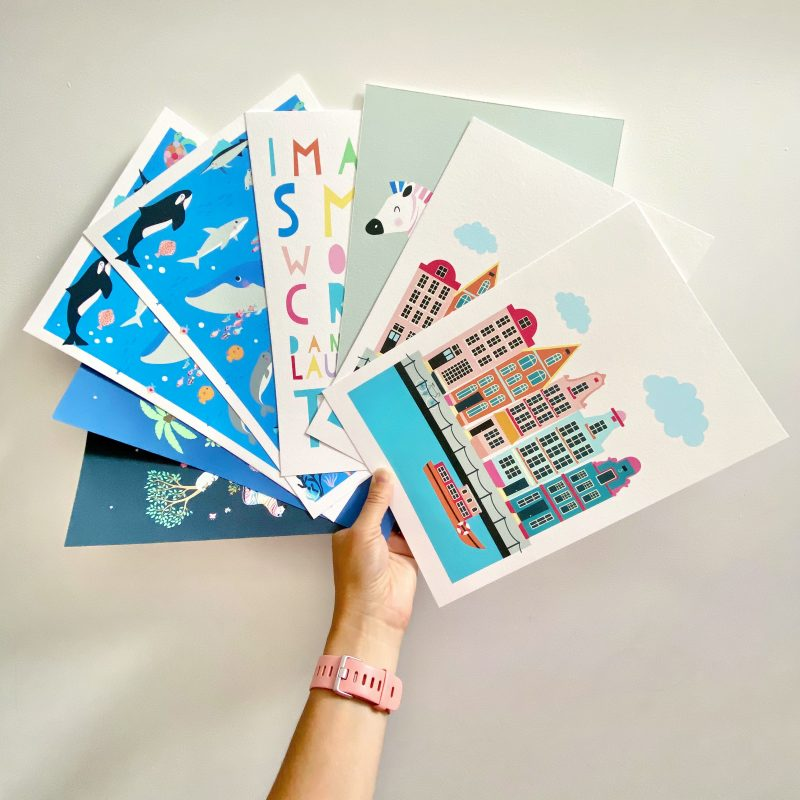 A hand holding a selection of colourful art prints