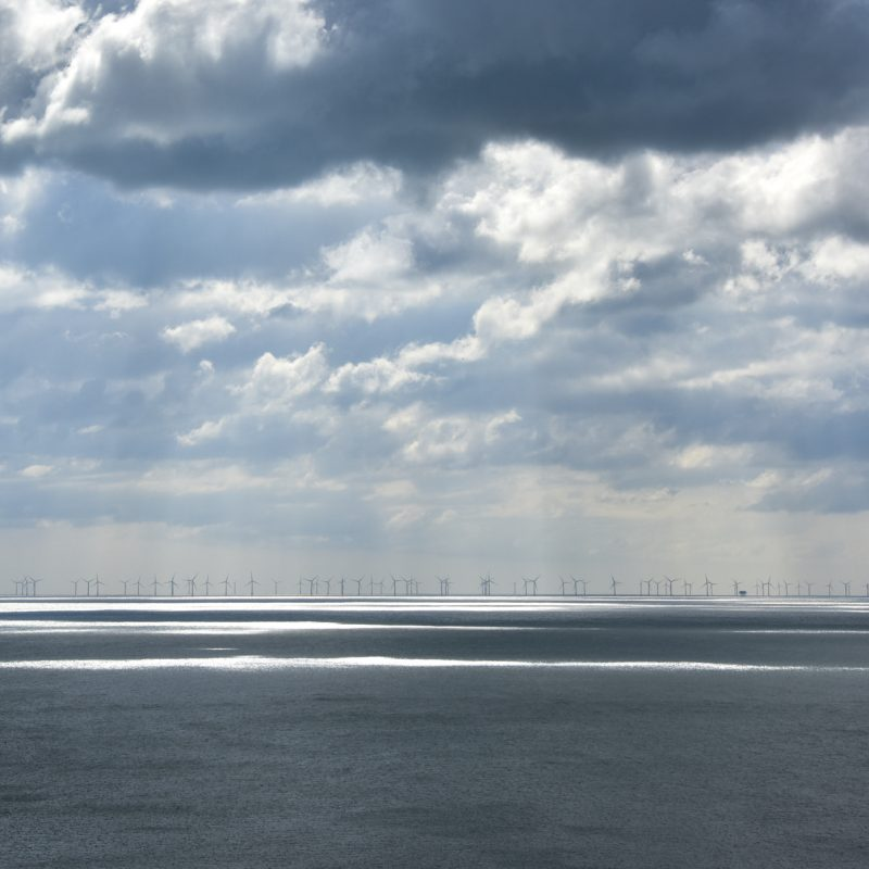 Cloudy seascape with sunlight beaming through onto the Rampion wind farm