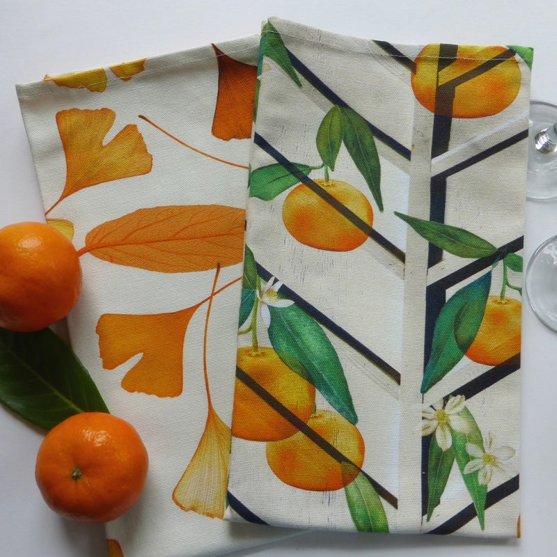 Bright Oranges with green leaves on a white cotton tea towel. Another tea towel is behind it with orange leaves.