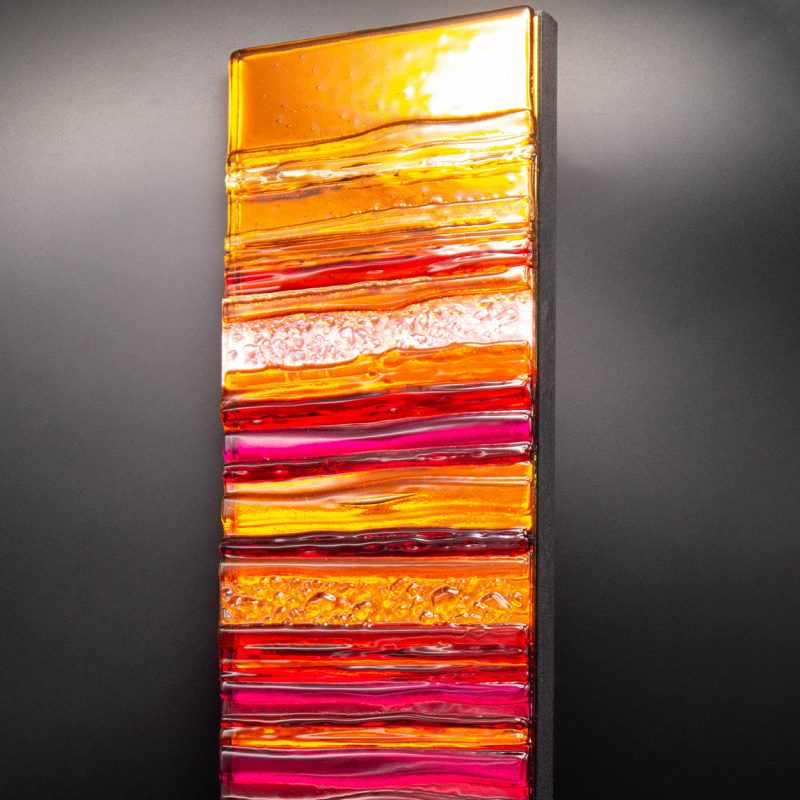 A stunning sculpted glass wall panel in sunset shades of orange, red and pink.