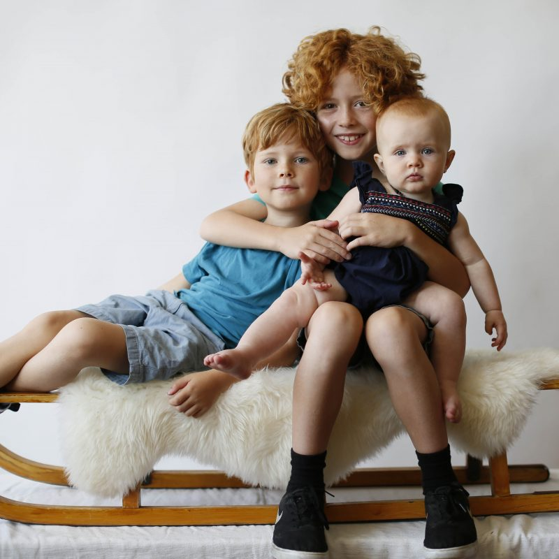 three red haired young children looking to camera