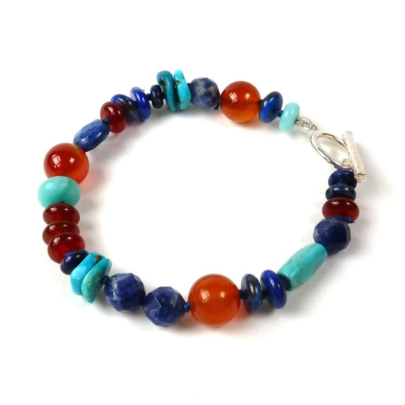 A unique bracelet hand-crafted from beads of carnelian, dumortierite, lapis lazuli, turquoise and amazonite. Individually knotted on blue thread.