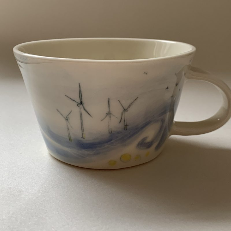 This unique porcelain mug is hand painted with images of the Rampion Wind Turbines  When making these illustrative ceramic pieces in my Brighton studio I work with porcelain. This gives me a smooth canvas for meticulous drawings of the South Downs and coast.  I work form memories and photographs as I hand paint and layer glazes onto my pieces.  This process takes many hours.  Currently I am working on a series of functional ceramic pieces that are inspired by the impact that we have on the land, from  barbed wire fences and pylons, to the Rampion Wind Turbines.  11 cm diameter x 7 cm height