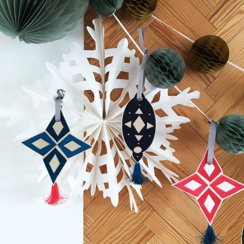 Paper Christmas decorations with hanging embroidered turquoise star with tassel, embroidered navy teardrop decoration with tassel and pink embroidered star with tassel.