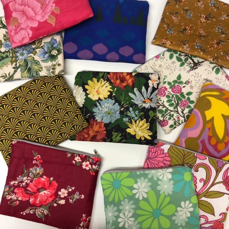 A selection of colourful make up bags including floral and geometric designs on a white background.