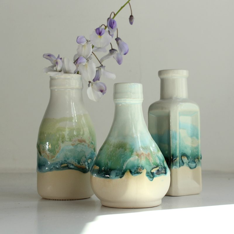 A set of three interesting shaped little bottle vases; white with hand painted green, turquoise and blue glazes.