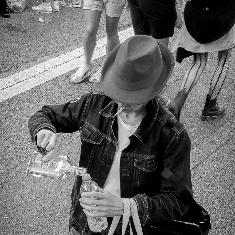A black and white photograph of a woman pouring vodka into a water bottle. Taken at Brighton Pride 2019