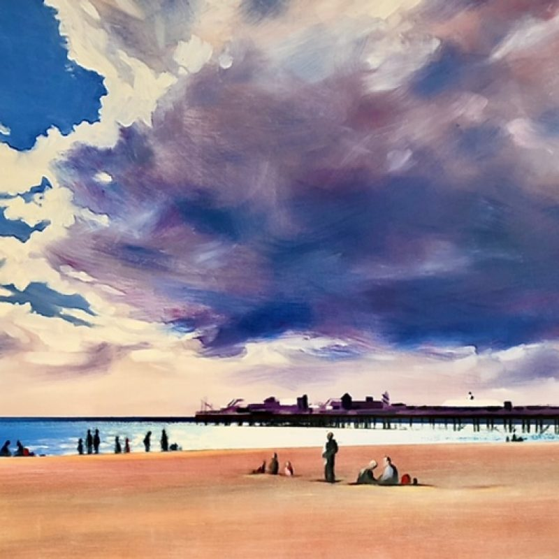 A view of Brighton beach with the Palace Pier in the background and dramatic cloud formations. People are sat on the beach and by the waters edge