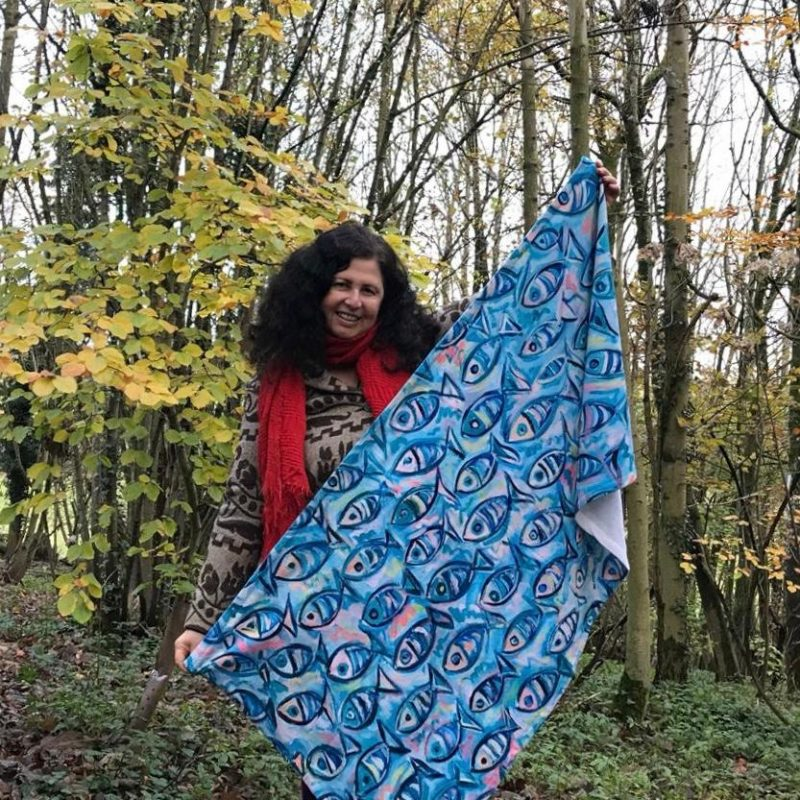 A picture of Orna holding a towel with colourful fiash painted on it.