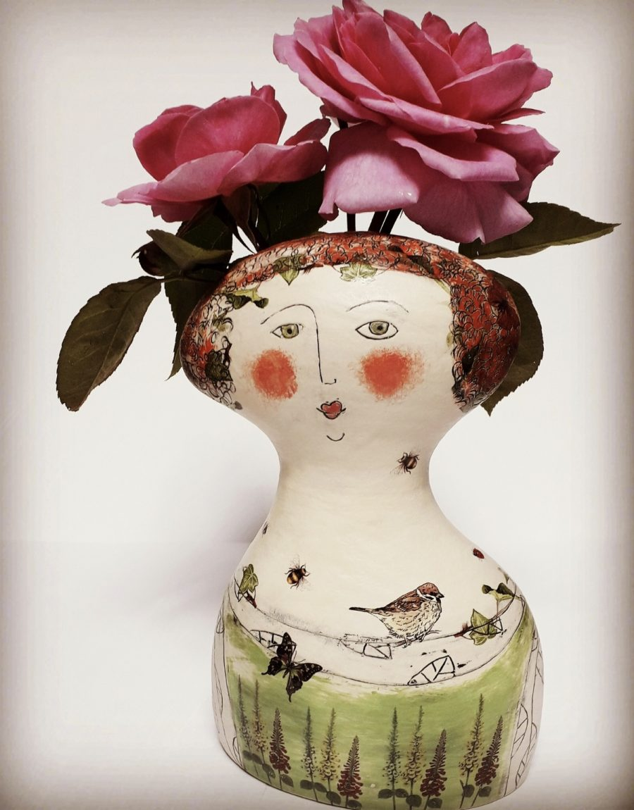 Vase shaped as a torso and head of a lady . Hand decoration with stencils of little birds and bees.