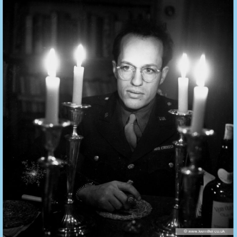 Black and white close up portrait of David E. Scherman at the dinner table wearing glasses and lost in thought, cigar in hand.. In the foreground are four silver candlesticks, lighted and bottles of wine. Bookcases are in the shadows behind him.