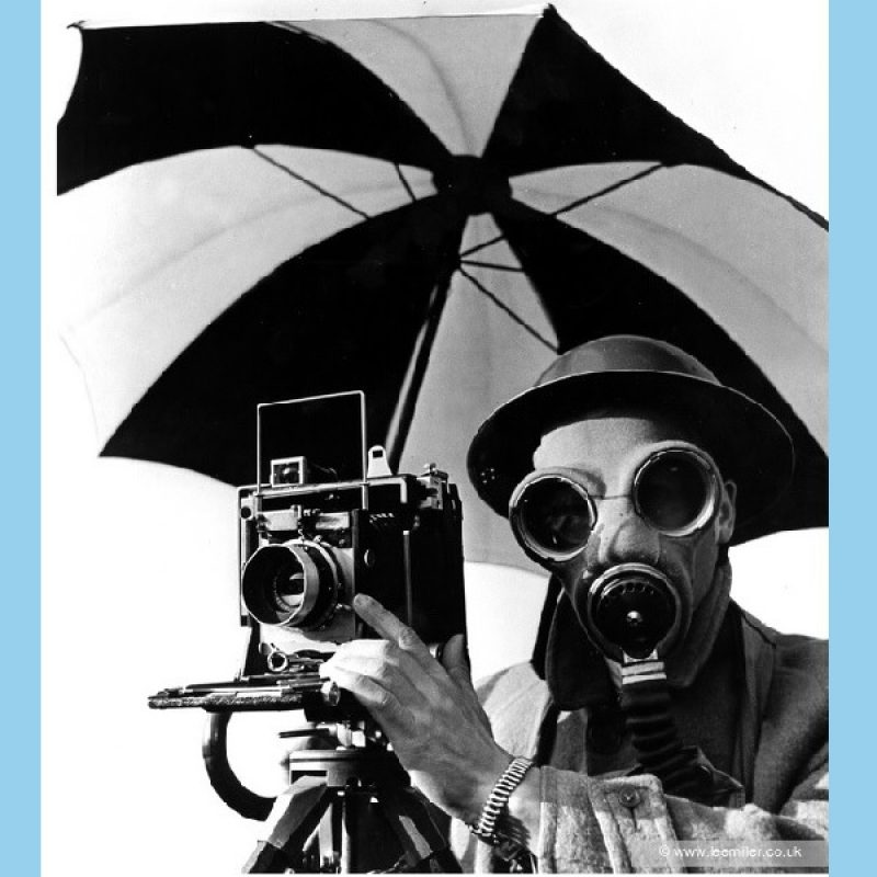 Black and white close up of David E. Scherman wearing tin hat, wool overcoat with upturned collar and gas mask, with camera on tripod, underneath umbrella.