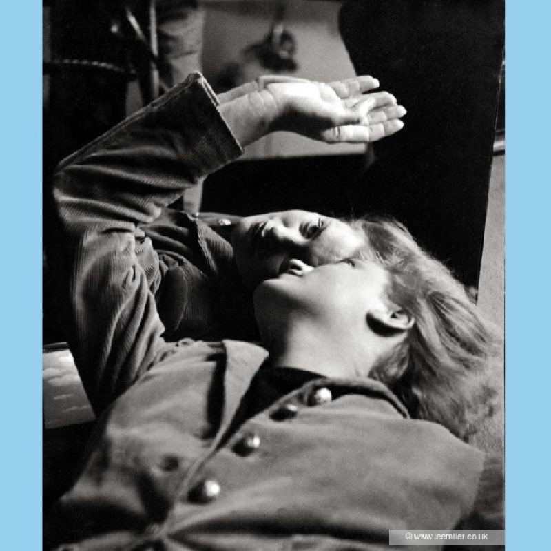 A black and white close up portrait of Lee Miller, lying down against a mirror, looking back towards her reflection, her hair loose. She is wearing a fitted corduroy jacket with brass buttons and her right arm is raised, her hand resting against the mirror.