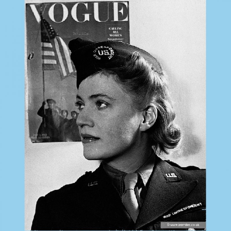 Black and white close-up portrait of Lee Miller in profile wearing uniform as an accredited war correspondent, looking very chic. On the wall behind her is a front cover of Vogue magazine depicting women with the American flag and the words