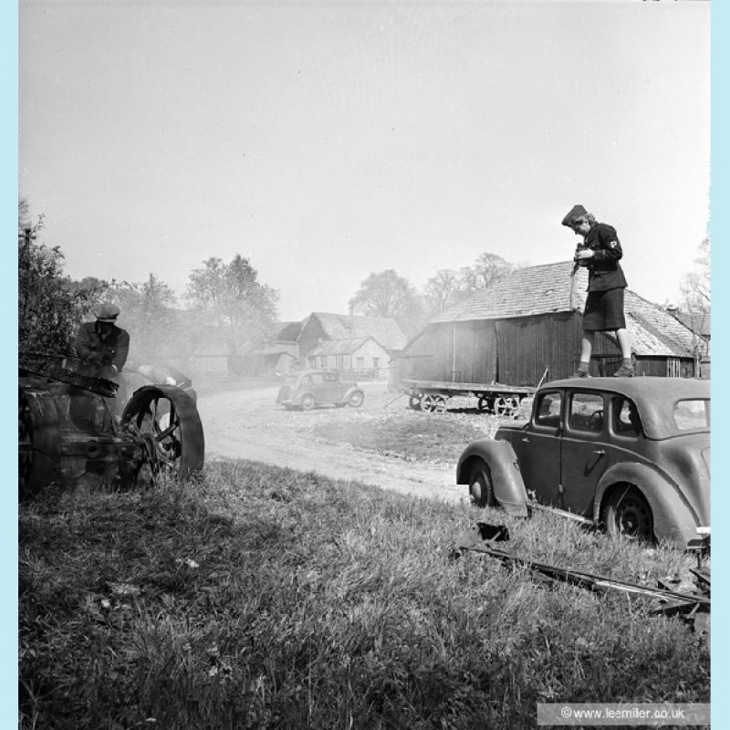 Black and white photograph of Lee Miller standing on top of a car, to right of picture, to photograph men working on a farm vehicle at the left of the picture, She is wearing her Press uniform. Smoke drifts over a car a farm trailer and agricultural buildings behind her.