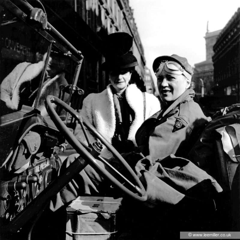 Black and white photograph of Lee Miller sitting in the passenger seat of a loaded jeep. She is looking towards the camera and squinting, she is in uniform with her hair hidden under her cap and goggles on her forehead. A very chic lady stands behind her, wearing a white coat and a tall black hat. The buildings of a Paris street can be glimpsed behind them.