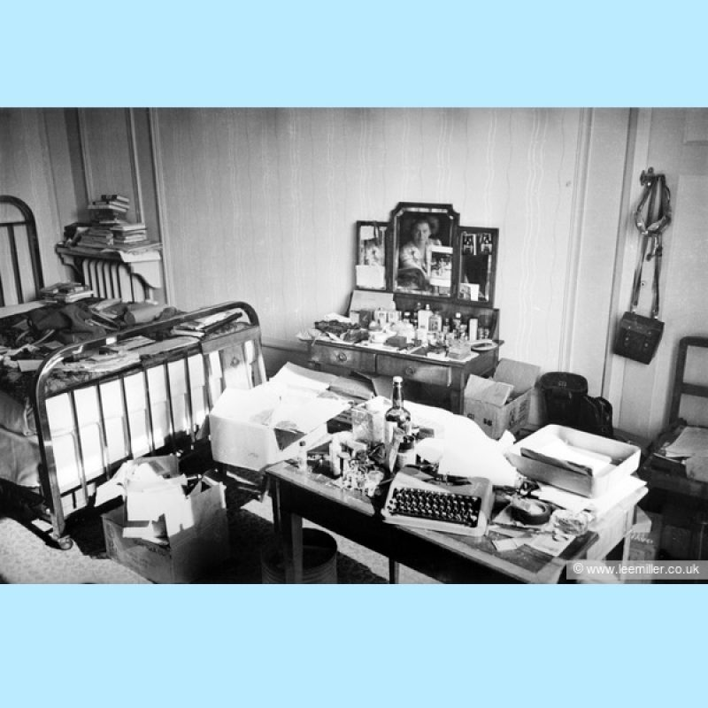 Black and white photograph of Lee Miller's very untidy hotel bedroom. Lee miller is reflected in the dressing table mirror. Every surface, including the bed and floor is covered with books, papers, equipment and paraphernalia. On a table in the foreground is her baby Hermes typewriter.