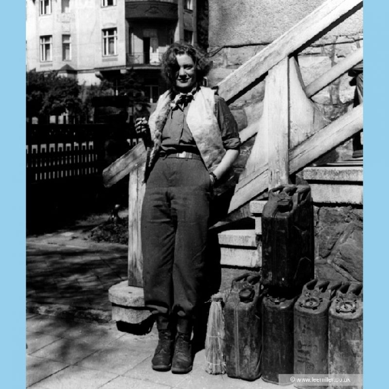 Black and white full length portrait of Lee Miller smiling, in casual dress; army boots, trousers, shirt with sleeves rolled up, waistcoat and neckerchief with cigarette in hand, leaning against the steps to a building. Beside her are petrol cans, behind her, beyond a fence are city buildings.