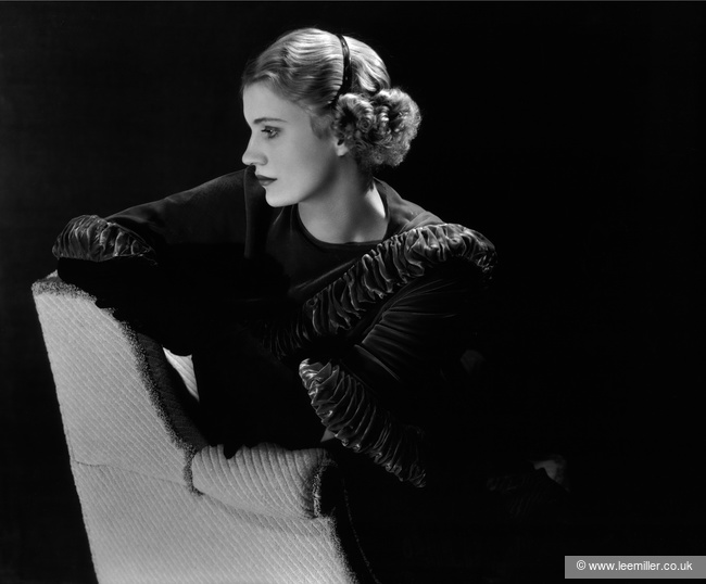 Self portrait of Lee Miller in profile, seated sideways on a chair, wearing a dark velvet ruffled shawl and a plastic headband.