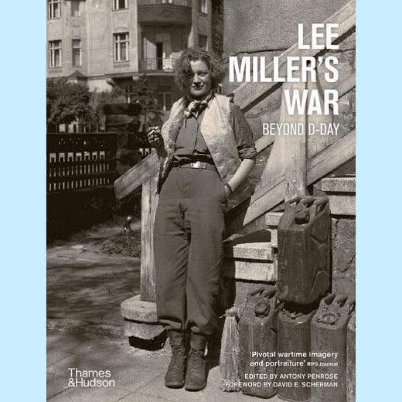 Book cover with black and white full length portrait of Lee Miller smiling, in casual dress; army boots, trousers, shirt with sleeves rolled up, waistcoat and neckerchief with cigarette in hand, leaning against the steps to a building. Beside her are petrol cans, behind her, beyond a fence are city buildings. Title Lee Miller's War: Beyond D Day