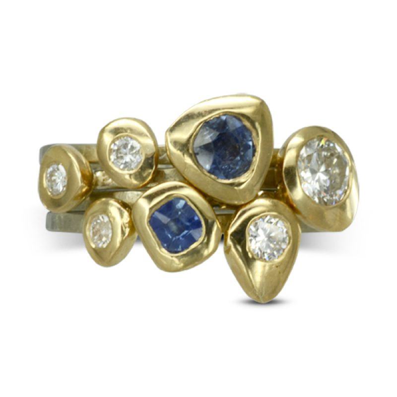 gold pebble shapes sitting on the top of three platinum rough hammered bands set with sapphires and diamonds
