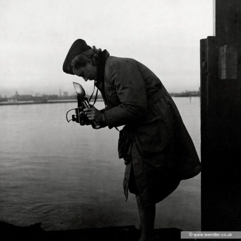 A full length black and white portrait of Lee Miller, almost in silhouette wearing uniform and mackintosh, leaning over her hand held camera with her flash gun ready. A background of water and distant dockside.