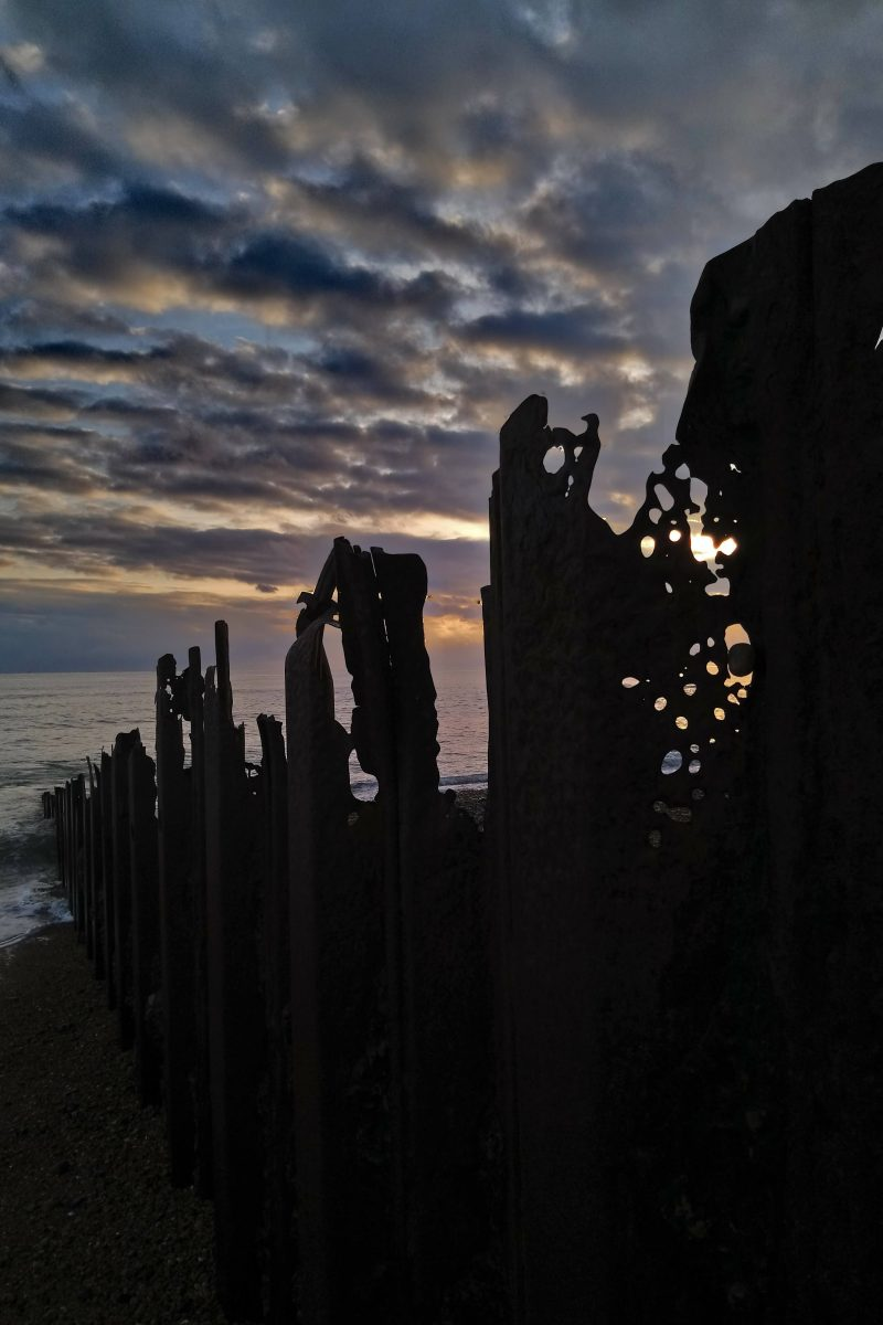Silhouette of rusting,decaying metal groyne against a sunset sky with marbled clouds
