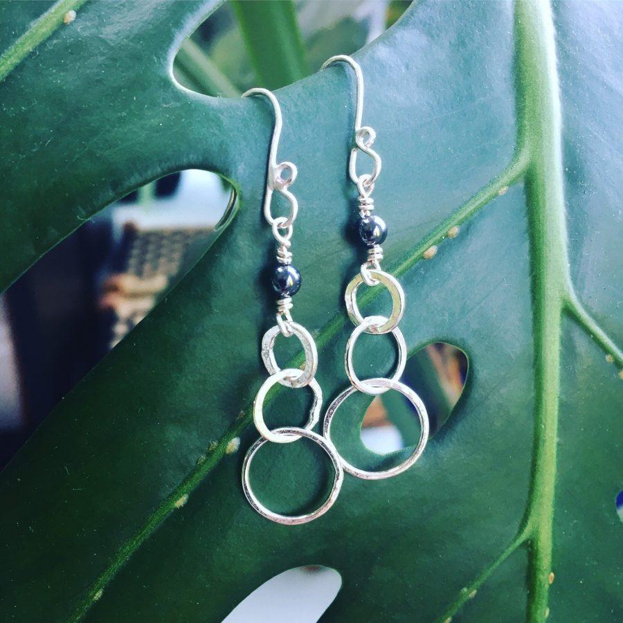 Silver drop earrings on a green leaf