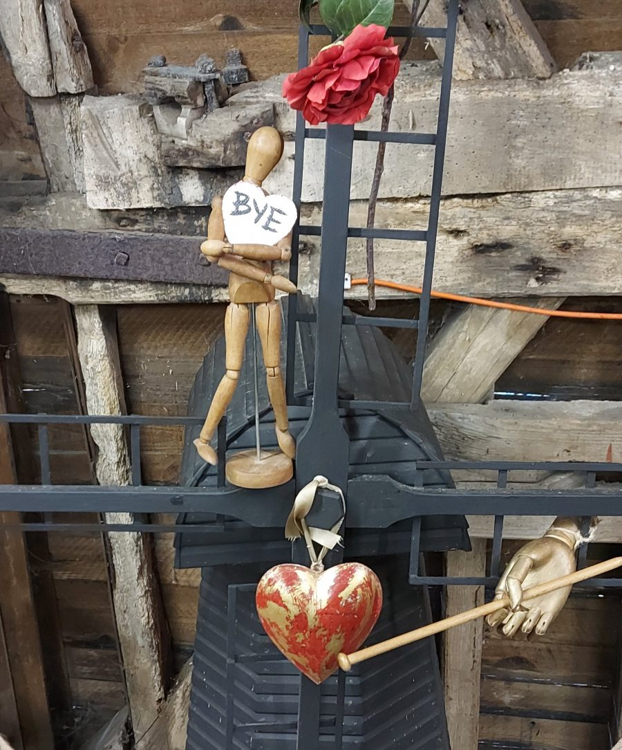 A Tin Heart being beaten by a drum stick, suspended on a model Windmill with a wooden Artist's  mannequin holding a paper heart with the word 'Bye'