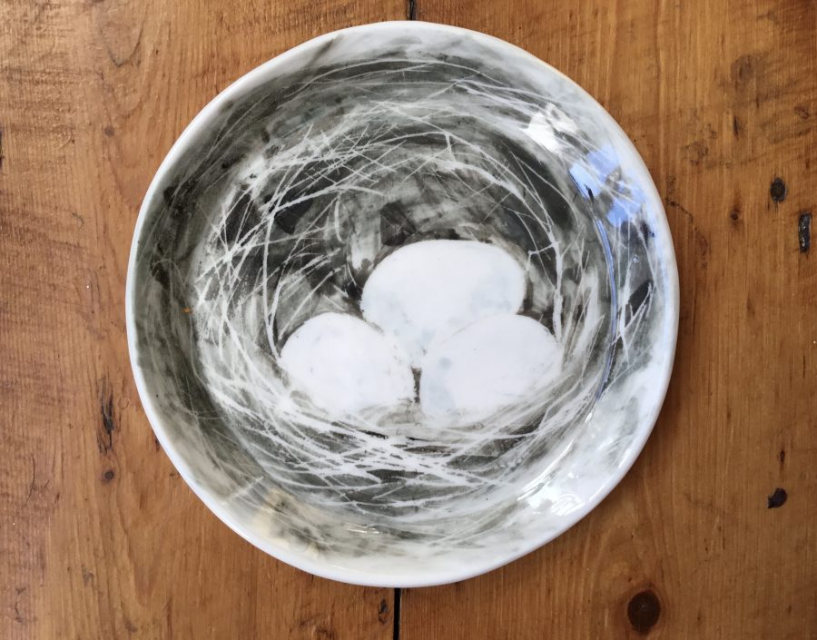 Porcelain plate with a painted image of a Robins nest with three pale blue eggs.