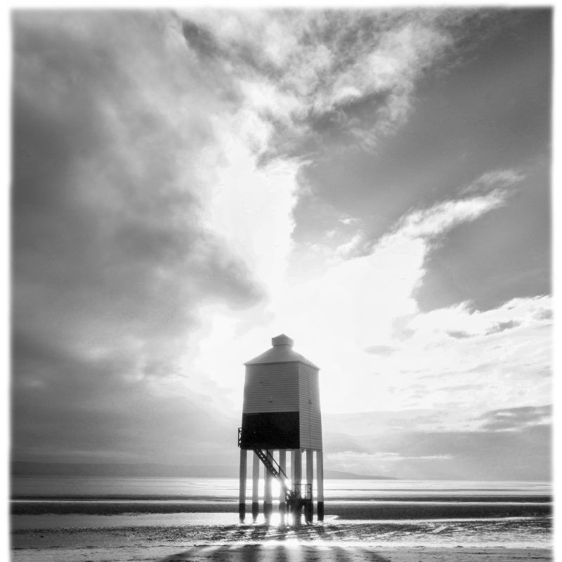 black and white photograph of a lights house on stilts on a sandy beach, casting long shadows