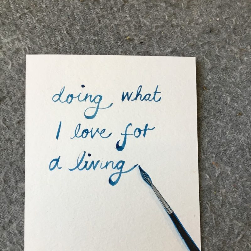 A paintbrush painted in the right hand side of the postcard, with writing in the middle stating 'doing what I love for a living'
