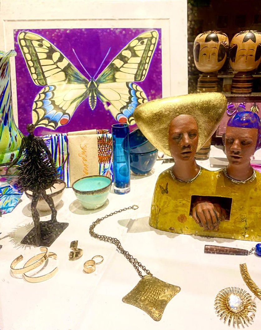 A compilation of artwork Scupture and jewellery including a large purple Butterfy print and two headed terracotta bust in yellow and gold.