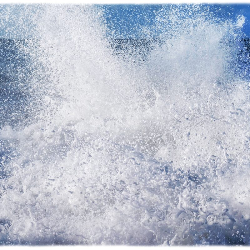 abstract photograph of a big wave crashing onto the beach