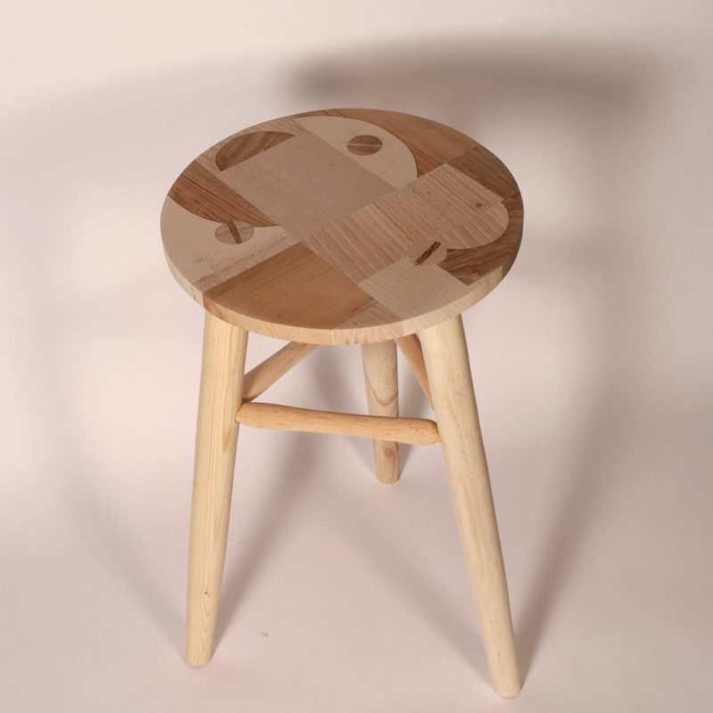 This stool is made from workshop offcuts of English hardwoods. The seat is made of a bold geometric created by the different tones of the hardwoods used. The stool is photographed against a soft pink background.
