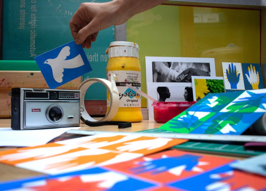 colourful prints are scattered on a tabletop surrounded by tools for screen printing and photography, yellow paint, screens, a squeegee, a roll of masking tape, a camera and a hand holding a screenprint of a white bird on a blue background.